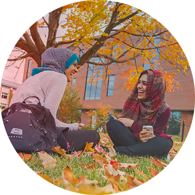 two students laughing on the lawn, UConn Storrs campus