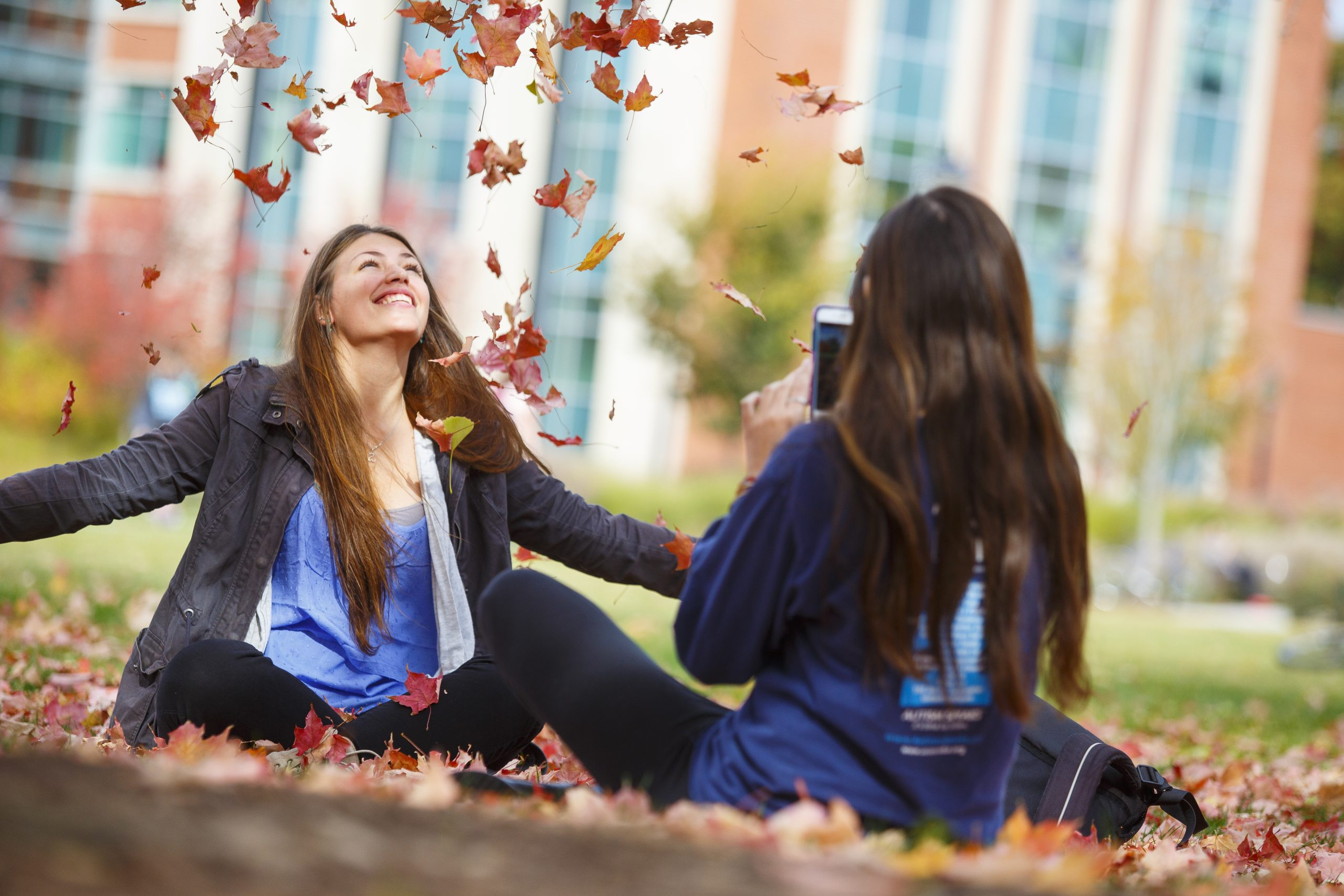 Student tossing leaves into the air